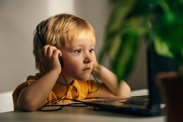 헤드폰을 끼고 관심 있는 어린 남학생이 집 책상에 앉아 비디오 튜토를 보고 있습니다