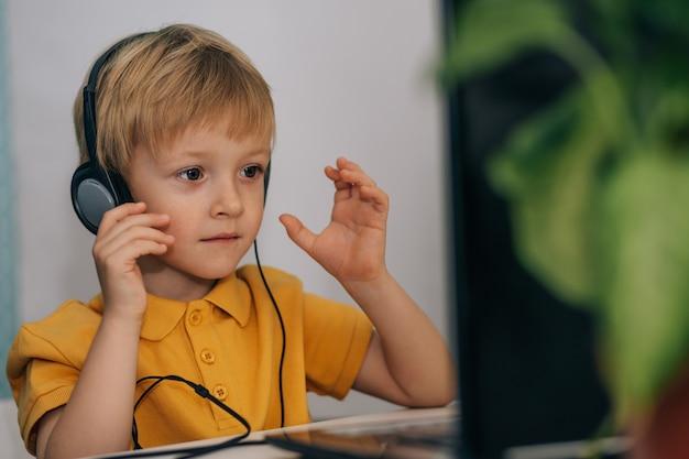 헤드폰을 끼고 관심 있는 작은 남학생이 집 테이블에 앉아 비디오를 보고 있습니다
