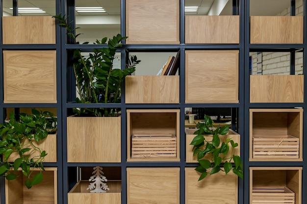 금속 검정색 구조, 나무 상자, 녹색 식물이 있는 냄비가 있는 건물 내부.