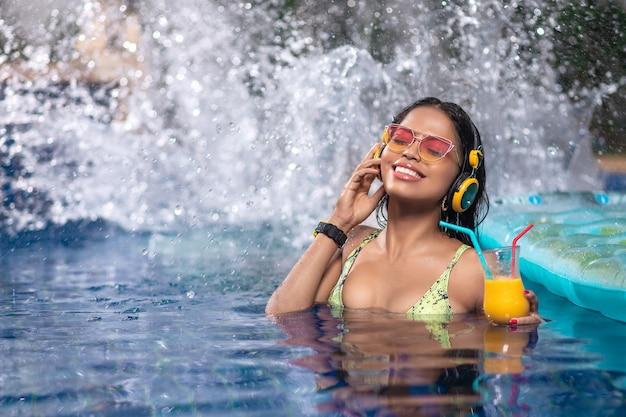 인종 간 갈색 머리는 그녀의 손에 칵테일과 매트리스에 구름의 수영장에서 즐기고있다