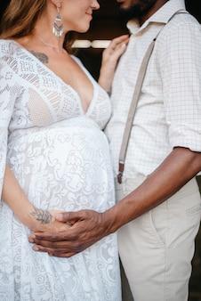 素朴なスタイルに身を包んだ異人種間のカップルが納屋に立っています