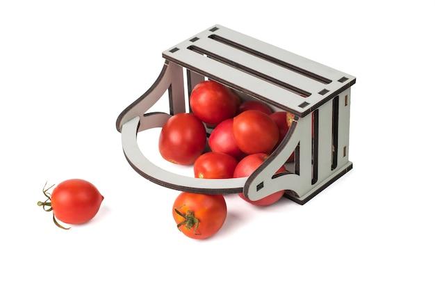 흰색 배경에 격리된 토마토가 있는 거꾸로 된 무너져가는 상자. 야채의 신선한 작물입니다.