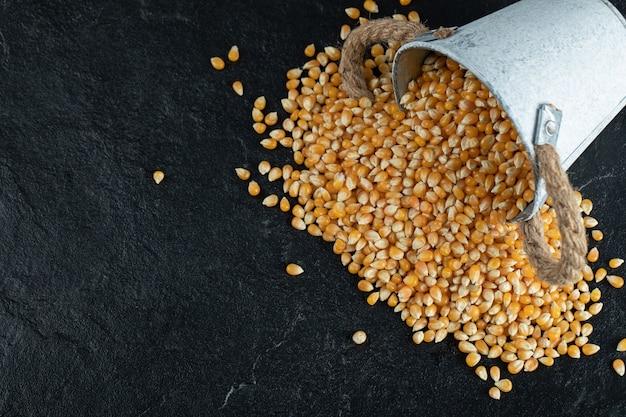 暗い表面に未調理のトウモロコシ粒が入った鉄製のバケツ