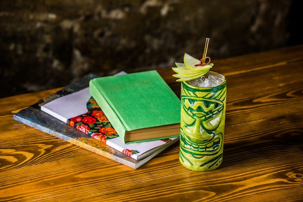 Железная банка лимонного сока со страшным лицом, трубочкой и дольками лимона.