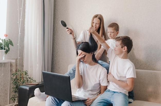 Раздраженная мама сидит на диване и работает дома на ноутбуке, активные дети играют с мамины волосы, делают ей прическу.
