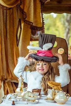 테이블에서 머리 위로 토끼처럼 귀로 실린더 모자를 들고 작은 아름다운 소녀