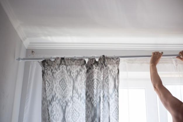 Мужчина вешает штору с занавеской на окно домашние дела и новый ремонт