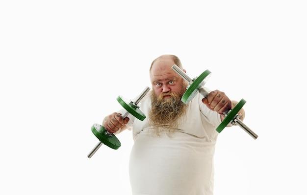 단호한 표정을 가진 뚱뚱한 수염 난 남자가 아령을 뻗는다.
