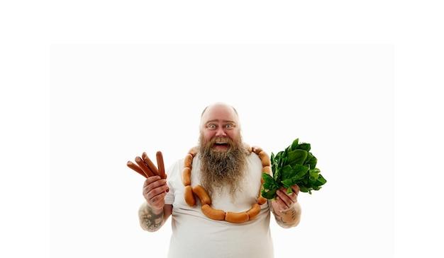 Тучный мужчина с сосисками на шее, держа в руках сосиски и шпинат. понятие о проблемах лишнего веса и здорового питания. изолированные на белом фоне