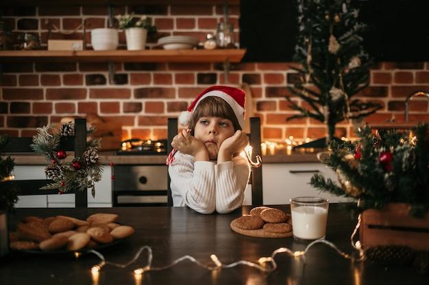 새해 모자를 쓴 화난 어린 소년이 테이블에 앉아 막대기에 다채로운 막대 사탕을 들고 있다