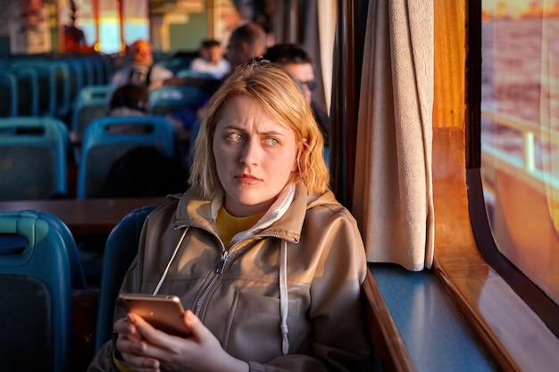 Обиженная молодая женщина сидит у окна в салоне парома и держит в руках смартфон.