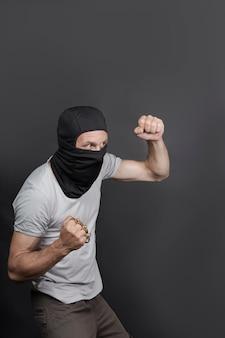 Атака нарушителя кастетом. металлические кастеты в руке кавказца в черной маске. запрещенное оружие в драке, преступное. американский мужчина показывает кулак костяшками пальцев. закрыть