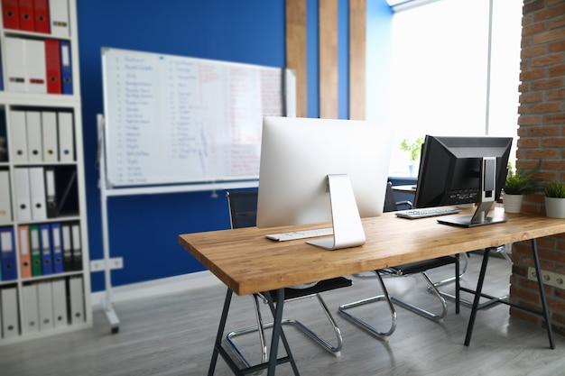 Офис, в котором находится рабочий стол компьютеров, белая информационная доска и шкаф с документами. планирование рабочего пространства в концепции офиса