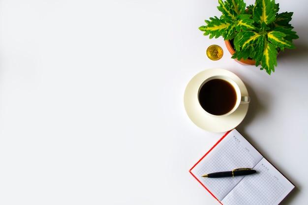 Офисный столик с чашкой кофе рядом с записной книжкой в красной записке, рядом зеленый цветок и б ...