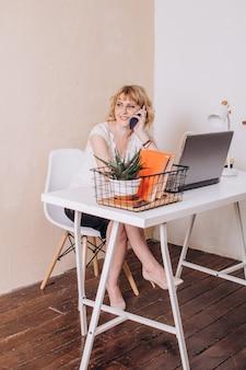 회사원은 노트북에서 일하고 앉아서 전화로 말한다