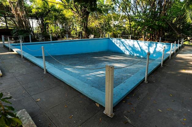 裏庭にある古い放棄された青いプール。未使用のプールを乾かします。秋。