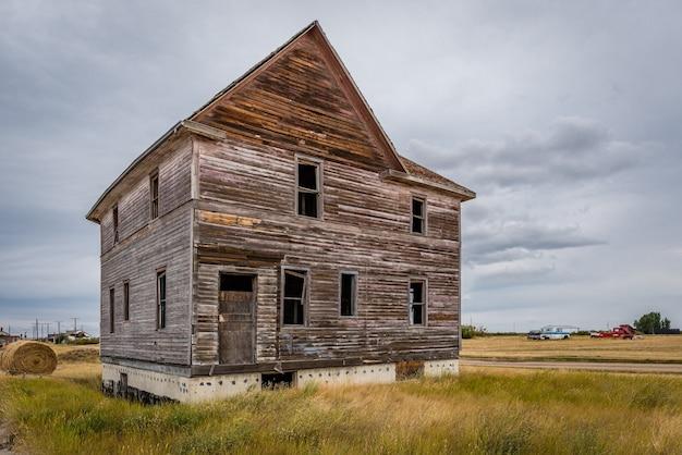 カナダの幽霊の町の背景にある古い廃屋と古典的なトラック