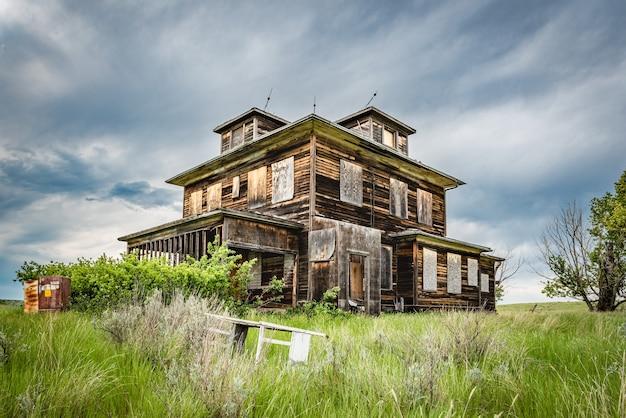 前景にベビーベッドがあるサスカチュワンの大草原にある古い廃屋 Premium写真