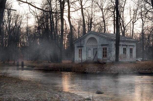 霧に包まれた神秘的な神秘的な公園の古い廃屋