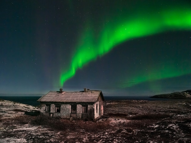 북쪽 별이 빛나는 하늘 아래 오래된 버려진 집. 오로라 보 리 얼리 스와 함께 밤 극지방 풍경.