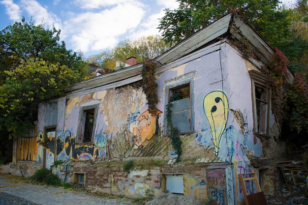녹색 잔디와 나무로 자란 낙서가 있는 버려진 폐허가 된 오래된 벽돌 집. 키예프, 우크라이나