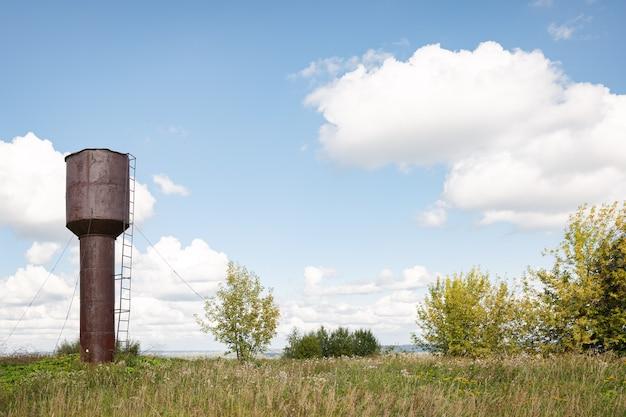 夏の象の日に緑の牧草地の真ん中に古い放棄された給水塔が立っています
