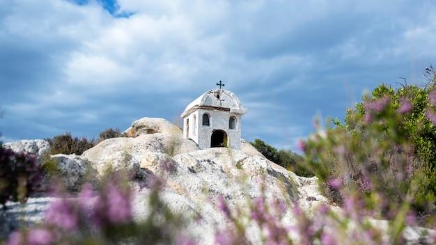 エーゲ海の海岸近くの岩の上にある古くて小さな神社、周りの茂み、曇り空、ギリシャ