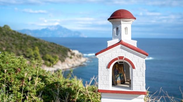 エーゲ海の海岸近くの岩、周りの茂み、水と山、ギリシャにある古くて小さな神社