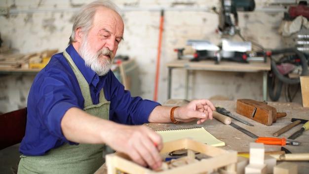 Старый ученик сидит за столом в своей мастерской и рисует эскиз деревянного изделия.