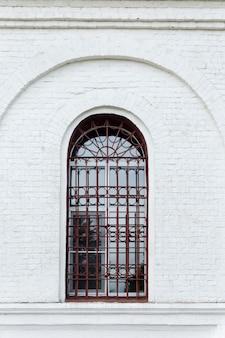 Старое арочное окно за решеткой в старом здании из белого кирпича. вертикальный.