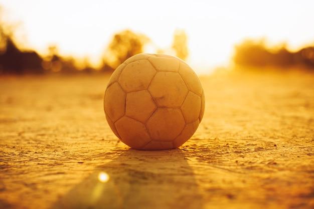 스포츠와 운동을 위한 일몰 빛 개념 아래 거리 축구 축구를 위한 오래된 공