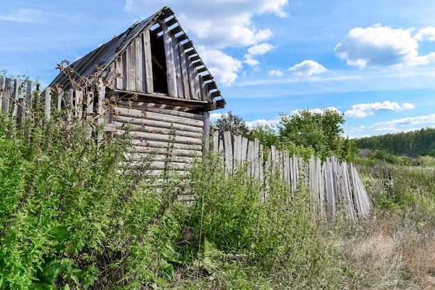 村の郊外にある古い納屋とフェンス