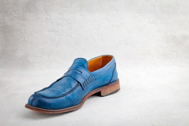 Старая синяя кожаная винтажная обувь на белом фоне
