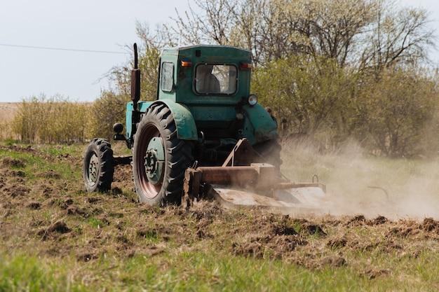 Старый синий трактор вспахивает поле и возделывает почву.