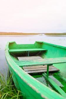 夏の湖の岸に古いボート