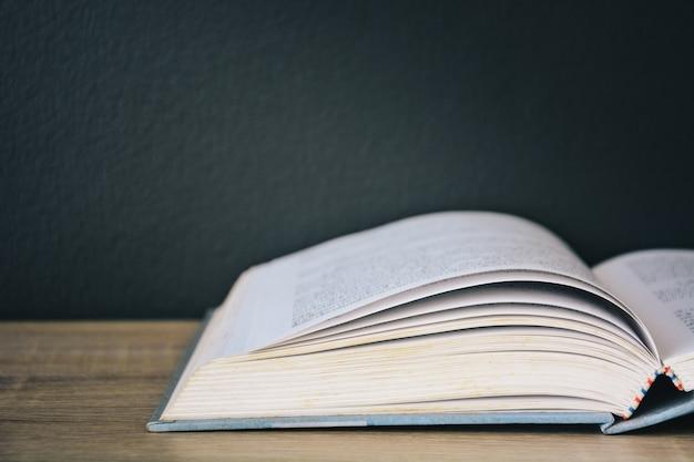 黒い色の壁の背景と上からの光と木製のテーブルで開く古い本