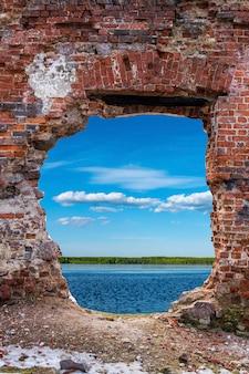 Старая кирпичная стена с аем посередине. водоем с небом на заднем плане. фото высокого качества