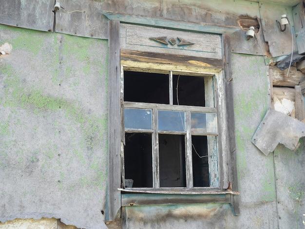 깨진 유리가 있는 마을에 있는 집의 오래된 깨진 창문. 버려진된 집입니다. 한 지방. 맑은 날