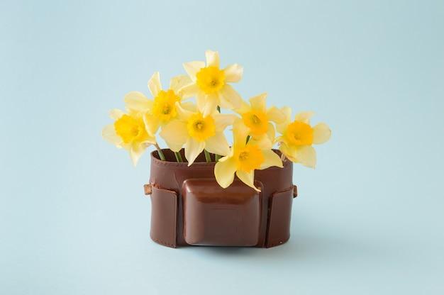 Старая коричневая сумка для фотоаппарата, наполненная желтыми цветами на синем фоне. концепция в стиле ретро.