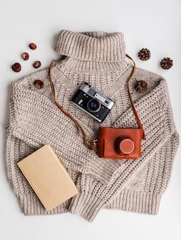 Старый фотоаппарат и книга на шерстяном свитере