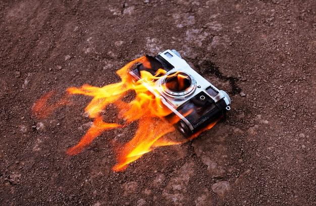 В пламени костра горит старый фотоаппарат. пожароопасность.