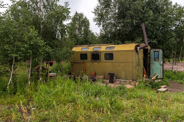 Старая автомобильная будка, переоборудованная в дом в лесу. зеленый железный сарай с окнами и дымоходом. дверь открыта. вокруг зеленые деревья и трава. по горизонтали.