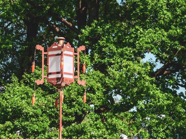 Старый китайский фонарь на зеленом дереве.