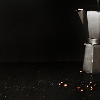 An old coffee maker with coffee beans on black background