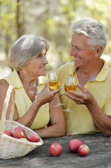 테이블에 와인과 과일 바구니를 마시는 노부부