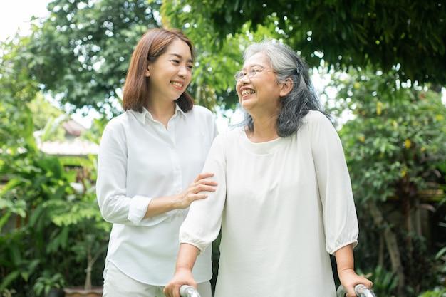 アジアの老婆が歩行器を使い、娘と一緒に裏庭を歩いています。