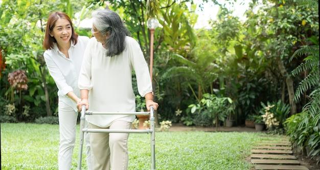Старая пожилая азиатская женщина использует ходунки и гуляет по заднему двору со своей дочерью