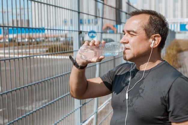 Пожилой старик пьет воду во время бега.