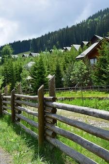 Старый бревенчатый забор возле речки, нескольких домов и деревьев. фото переходит в перспективу