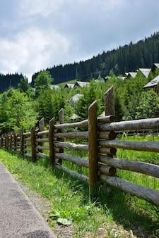 Старый бревенчатый забор возле речки, нескольких домов и деревьев.